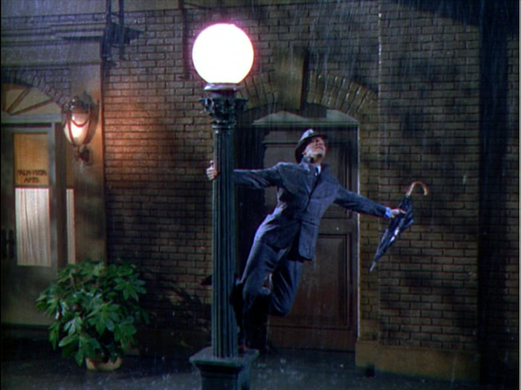 Gene Kelly in navy suit wearing fedora hat holds rolled umbrella in extended left hand and swings off lit lamppost with the other as he sings in the rain